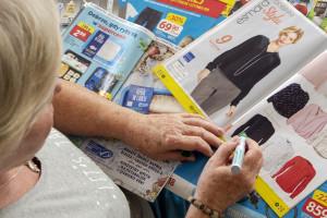 Seniorzy analizują gazetki handlowe przed dokonaniem zakupów